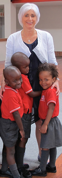 Three children give Jill a hug during her visit to their class in South Africa